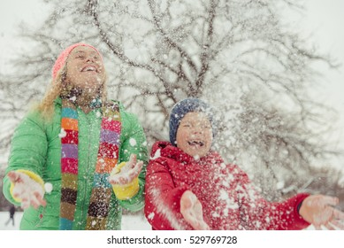 Winter. Mom with a child playing with snow.