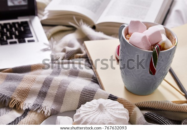 Winter mood Christmas Day at home with cup of hot cacao or coffee with marshmallow sweets candy cane and lollipop read book with films at laptop work in the bed with wool knitted plaid New Year.