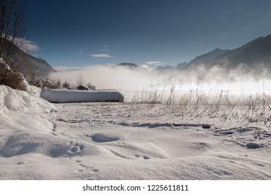 Winter morning, a fog lies over the lake Weissensee, Carinthia, Alps, Austria