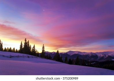 Winter morning landscape. The sun rises behind trees and lights up the clouds. Mountain ridge. The moon In the sky. Wooden fence in snowy field. Twilight. Purple colors. Romantic mood