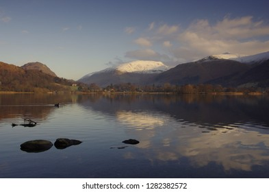 Winter morning on Grasmere with calm mountain reflections on the lake