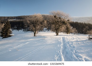 winter morning with snow, hiking trail, few chalets and clear sky on Butoranka bellow Lysa hora hill in Moravskoslezske Beskydy mountains in Czech republic