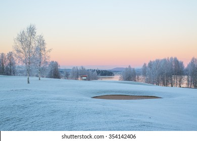 Winter morning with sunrise on a golf course where the greens are covered with frost over the green bottom.