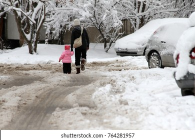 Winter. Mother and kid walks hard on a snowy icy road after a heavy snowfall in the city, uncleaned icy road, icy roads. icy streets