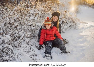 winter Mother and son throwing snowball at camera smiling happy having fun outdoors on snowing winter day playing in snow. Cute playful young woman outdoor enjoying first snow