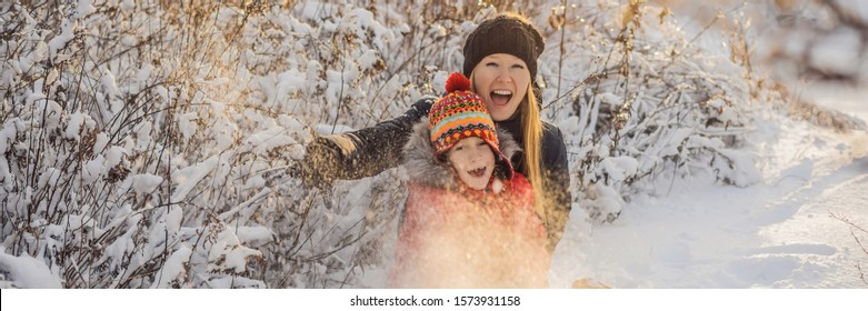 winter Mother and son throwing snowball at camera smiling happy having fun outdoors on snowing winter day playing in snow. Cute playful young woman outdoor enjoying first snow BANNER, LONG FORMAT