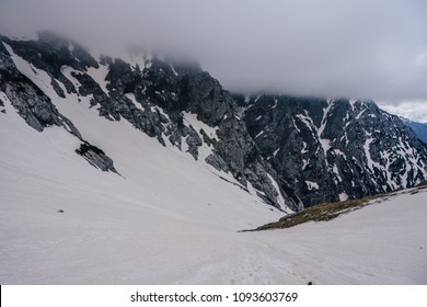 Winter mountain alpine landscape of Kamnik-Savinje alps, Slovenia. An alpine summit covered with snow, dramatic sky with clouds. Alpine adventure ascent in the alps. View to the valley