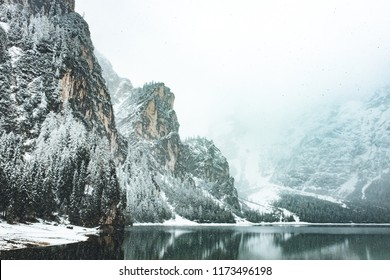 Winter in mountain lake area, fog over mountains, moody nature landscape
