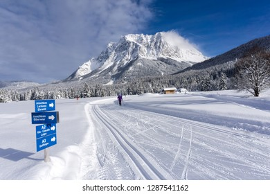 Winter mountain landscape with groomed ski trails and blue sky in sunny day. Ehrwald valley, Tirol, Alps, Austria, Zugspitze Massif  in background.