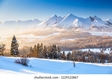 Winter mountain landscape. High mountains peaks with snow illuminated by bright morning sun through mist. Winter mountain background.