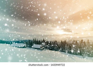 Winter mountain landscape. Old wooden houses on snowy clearing on background of mountain ridge, spruce forest and cloudy sky. Happy New Year and Merry Christmas card.