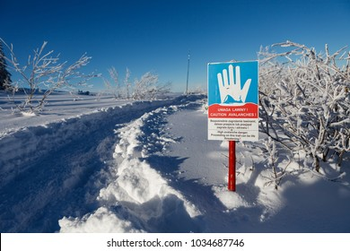 """Winter mountain landscape, sign """"caution avalanches"""", route from Hala Gasienicowa, Tatry Mountains, Poland"""