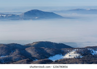 Winter mountain landscape with snowy foggy valleys in the morning, view from Postavaru peak, Poiana Brasov, Romania.