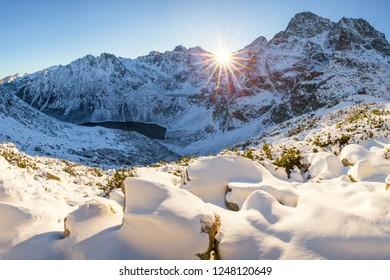 Winter mountain landscape. Sun shines through mountain peak at snowy hills. Winter scene in Tatra mountains, Poland.