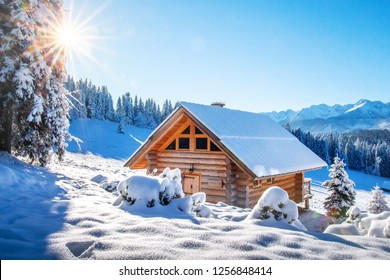 Winter mountain landscape with wooden house on sunny clear day. Alpine village in snowy mountains. Frosty morning in Alps, Switzerland.