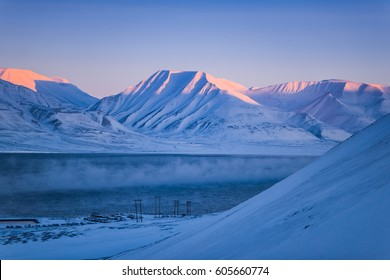 Winter mountain nature Svalbard Longyearbyen Svalbard Norway with blue sky and snowy peaks  on a sunny day  wallpaper during sunset sunrise orange fire