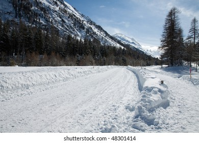 Winter Mountain Panorama on Alps full of snow and ice. Road inside the snow