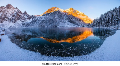 Winter mountain panoramic landscape. Mountain peaks illuminated with morning sunlight and reflected in clear lake. Stunning winter natural background. Tatras mountains. Winter wonderland.