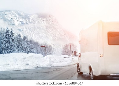 Winter mountain road landscape with campervan turning aside. Family vacation travel, holiday trip in motorhome. Beautiful austrian nature scene