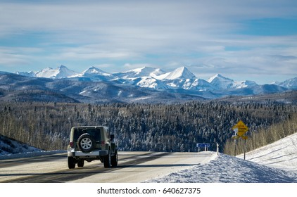 Winter mountain road with Rocky Mountains in a background, Alberta, Canada