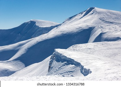 Winter mountain view with summits and valley