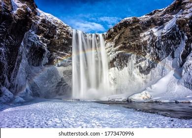 Winter mountain waterfall snow scene. Snowy mountain waterfall landscape. Winter mountain waterfall rainbow