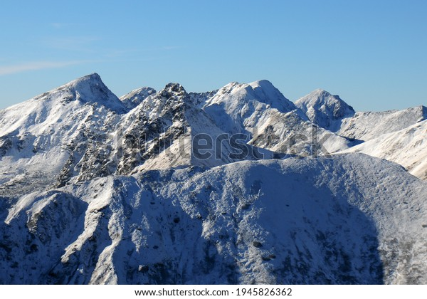 Winter in the mountains. Forests and ridges covered with snow - panorama of Western Tatras. High Tatras national park, Slovakia. Sunny day with blue sky.