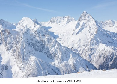 Winter mountains with high peaks. Snowboarding and skiing, enjoying the snowy landscapes. Lifestyle snowboarding, adventure, sports and travel.