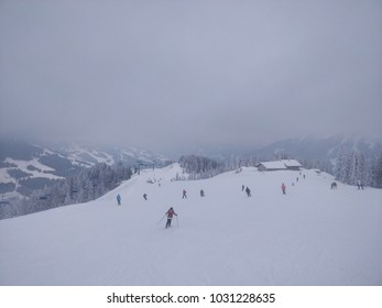Winter mountains panorama on a foggy day with many skiers and snowboarders, Austrian Alps
