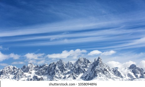 Winter mountains, panorama - snow-capped peaks of the Italian Alps. Dolomites, Alps, Italy, Trentino Alto Adige. Snow-capped mountains. Winter landscape. Panorama of snowy mountains in clouds.