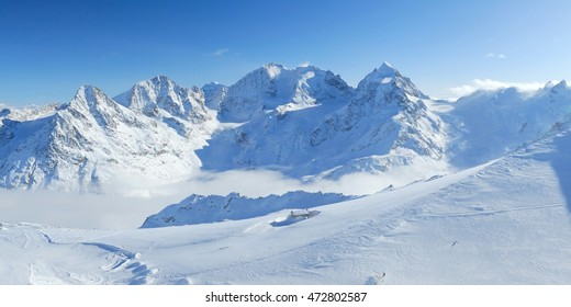 Winter mountains panoramic view with clouds in the valley and small hut. Corvatsch, Engadin, Switzerland.