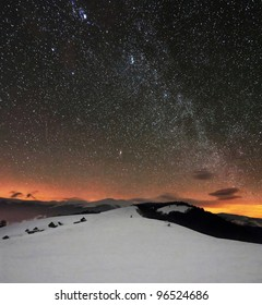 winter mountains under starry cloudy sky with milky way