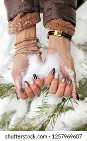 Winter multicolored manicure with snow in the hands of a girl with bracelets close-up on the background of snow and pine branches.Nail art.