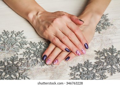 Winter nail art with purple and pink colors on wooden background