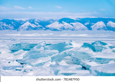 Winter nature landscape of blue Ice on the Frozen Lake Baikal with mountains on the background. Beautiful frozen lake and big ice plates covering with snow. turquoise blue ice in sub zero condition.