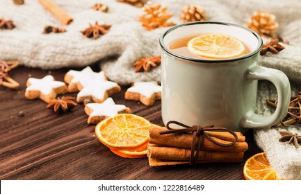 Winter and New Year theme. Christmas tea with spices, cup of tea with orange, cinnamon, anise, cookies in a shape of star, fir cones, pepper and gray scarf on wooden background. Copy space for text.