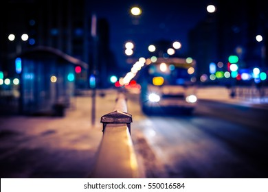 Winter night in the big city, the bus arrives at the bus stop. Close up view from the handrail on the sidewalk level, image vignetting and the yellow-blue toning