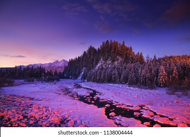 Winter night landscape. Colorful night nature in mountains. Sky with stars over snowy riversides.