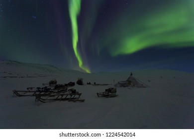 Winter night landscape with sledges, choom and aurora in the sky. The Yamal Peninsula. Russia
