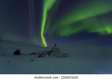Winter night landscape with sledges,choom and aurora borealis in the sky. The Yamal Peninsula. Russia