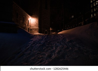 An winter night out in a lane of Montreal, Quebec. Where a Single light glows made a faint reflection on fresh snow. Low light made a lone eerie feel.