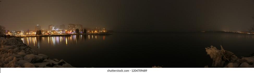 Winter night panorama, city lights and a dark lake