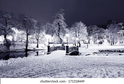 Winter night park with bridge and city channel in Old Riga, Latvia