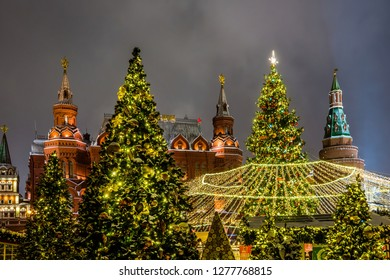 Winter night view of the big Christmas tree and decoration on the Manezhnaya square with the State historical Museum, Iverskaya chapel and Uglovaya Arsenal'naya tower of Kremlin in Moscow, Russia.