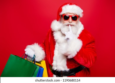Winter noel eve Christmastime black Friday. Excited hearsay news mature aged grandfather Santa in gloves spectacles white beard package hold forefinger near lips quiet sign isolated red background