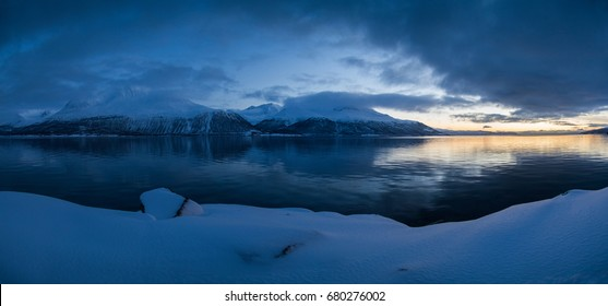 Winter norwegian mountains panorama with reflection in the still fjord