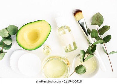 Winter nourishing skincare. Fresh avocado face mask and bowls of healing oil, green aromatic eucalyptus plant leaves. Natural beauty treatment ingredients, flat lay.