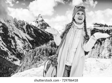 Winter on higher level of fun. smiling modern traveller woman in the front of mountain landscape in Alto Adige, Italy catching snowflakes