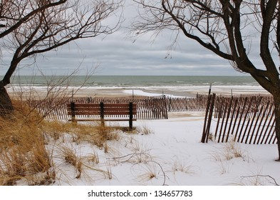 Winter on the Lakes. Park bench framed by bare tree branches on a winter beach. Port Crescent State Park. Port Austin, Michigan.