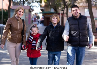 Winter outdoor portrait of happy family with son and daughter